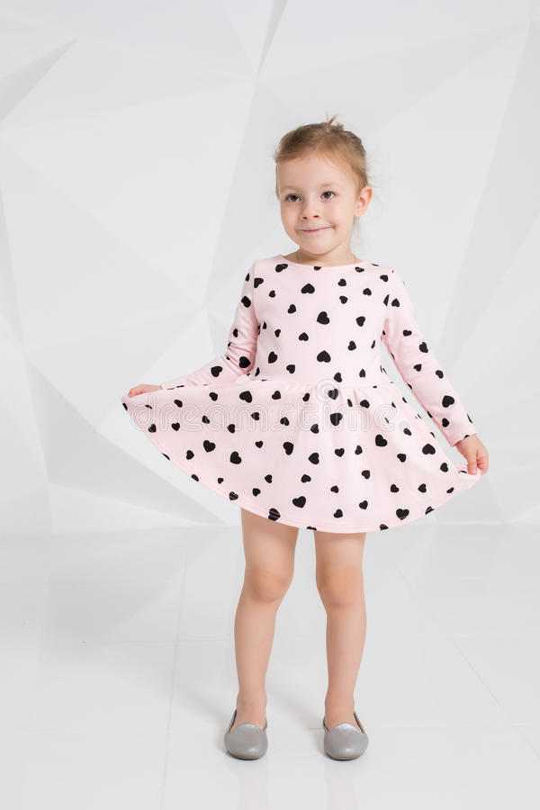 Beautiful little fashion model on white studio background. Portrait of cute girl posing in studio. Little blonde in a gently pink dress with hearts royalty free stock photo