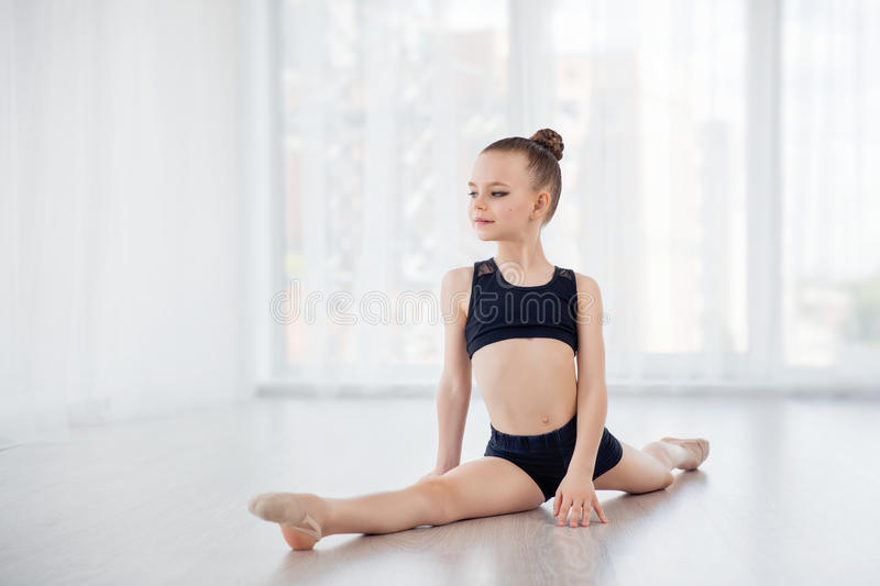 Beautiful little fit gymnast girl doing gymnastic exercises or exercising in fitness class royalty free stock photo