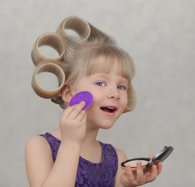 Beautiful little girl applying make up royalty free stock photo