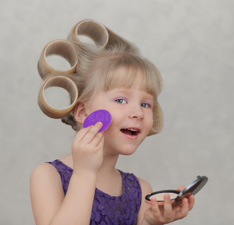 Beautiful little girl applying make up. Beautiful little girl in a violet dress applying make up royalty free stock photo