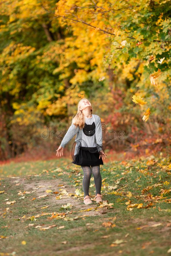 Beautiful little girl with autumn leaves in the park. Beautiful little girl jumping with autumn leaves in the park outdoor royalty free stock photography