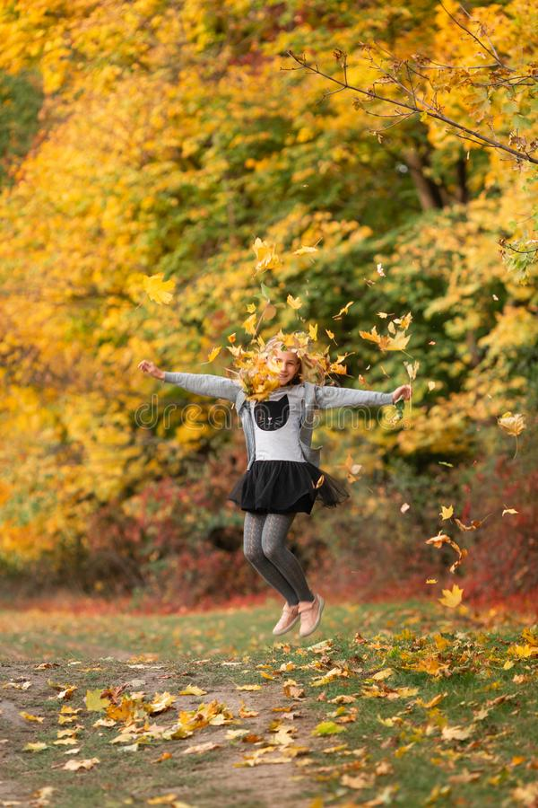 Beautiful little girl with autumn leaves in the park. Beautiful little girl jumping with autumn leaves in the park outdoor stock photography