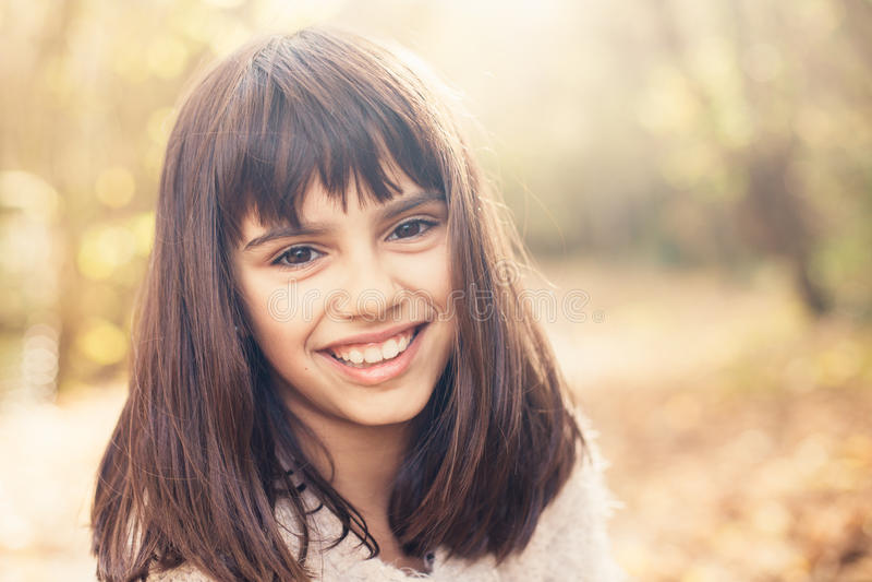 Beautiful little girl in autumn. Portrait of a beautiful happy little girl outdoors in autumn stock photo