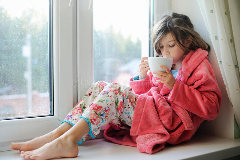 Beautiful little girl in bathrobe with cup of tea stock photos