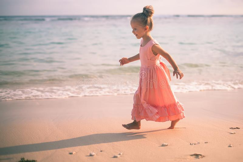 Beautiful little girl at the beach. Sunblock cream for children. royalty free stock image