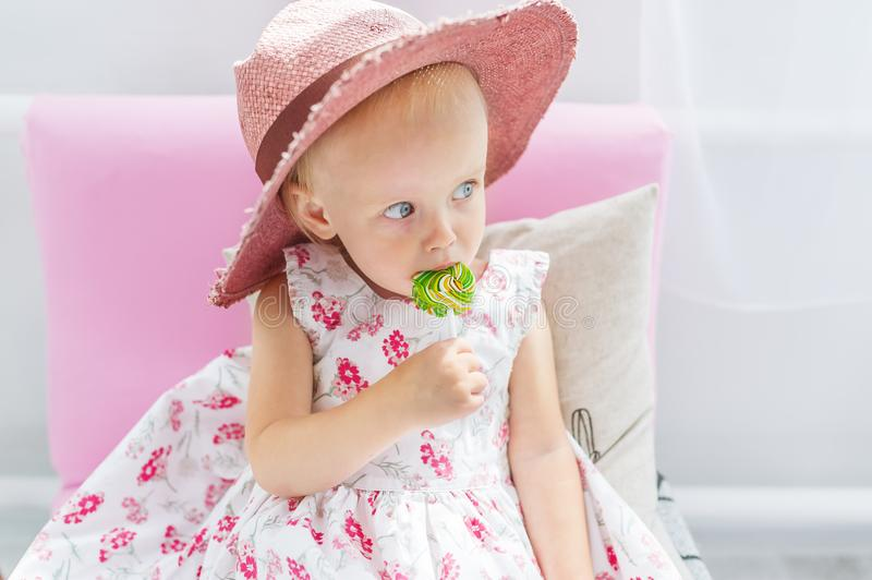 The beautiful little girl in a big hat sucks lollipop sitting on a sofa. Closeup portrait stock images