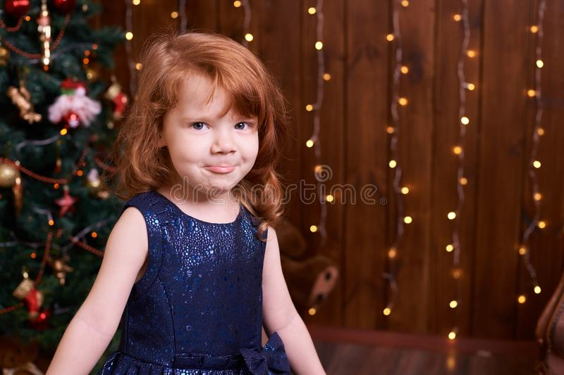 Beautiful little girl. Blue dress. Christmas interior royalty free stock images