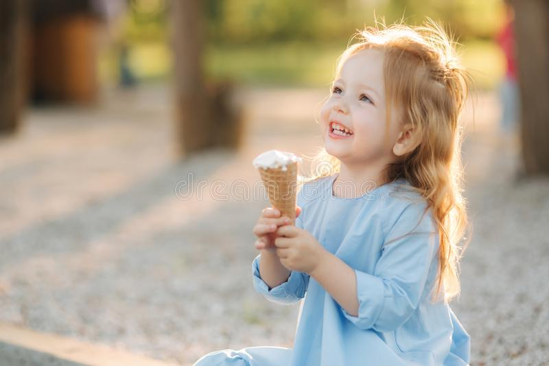 Beautiful little girl in a blue dress eating an ice cream stock image