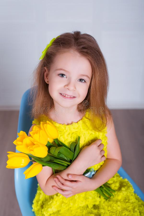 Beautiful little girl with a bouquet of tulips. Spring and summer portrait of cute child holding flowers. royalty free stock photography