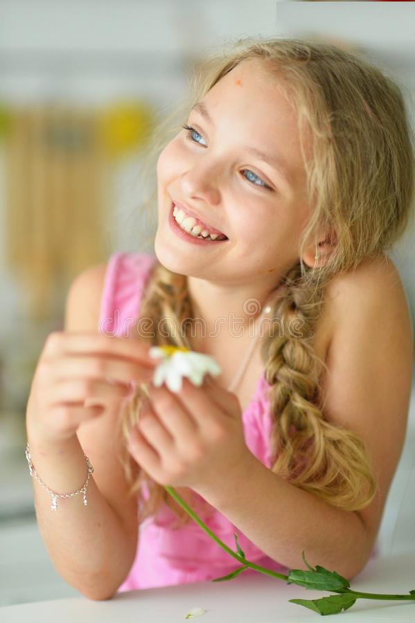 Portrait of beautiful little girl with braids holding white flower. Beautiful little girl with braids holding white flower at home stock photography