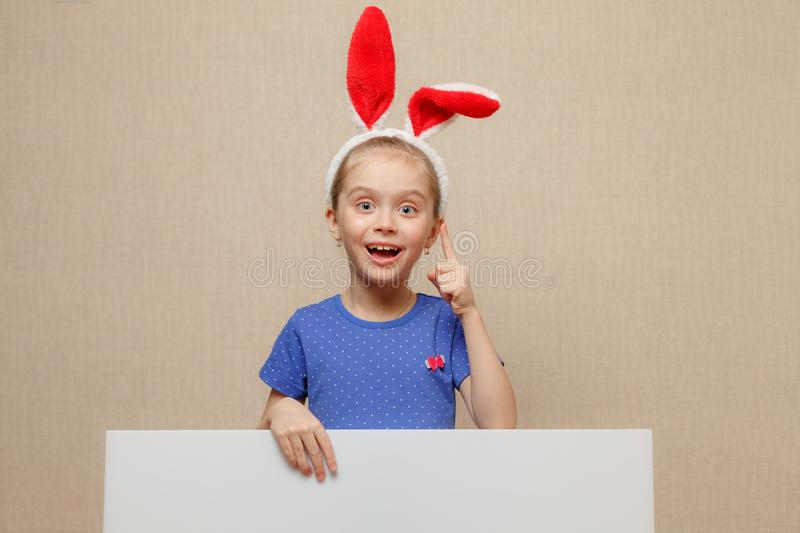 Beautiful little girl with bunny ears and blank banner. Happy easter royalty free stock photo