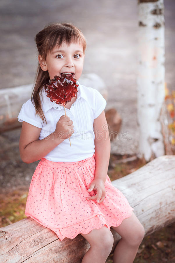 Beautiful little girl with candy stock images