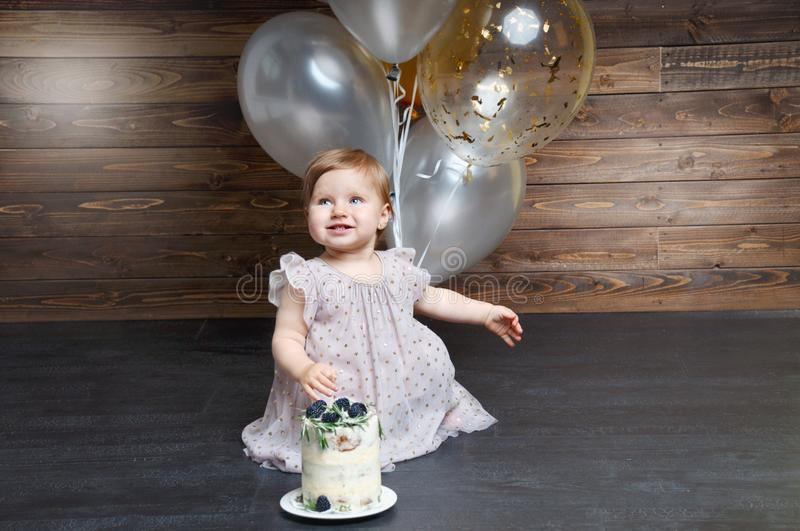 Beautiful little girl celebrating birthday party with balloons and birtday cake. stock photography
