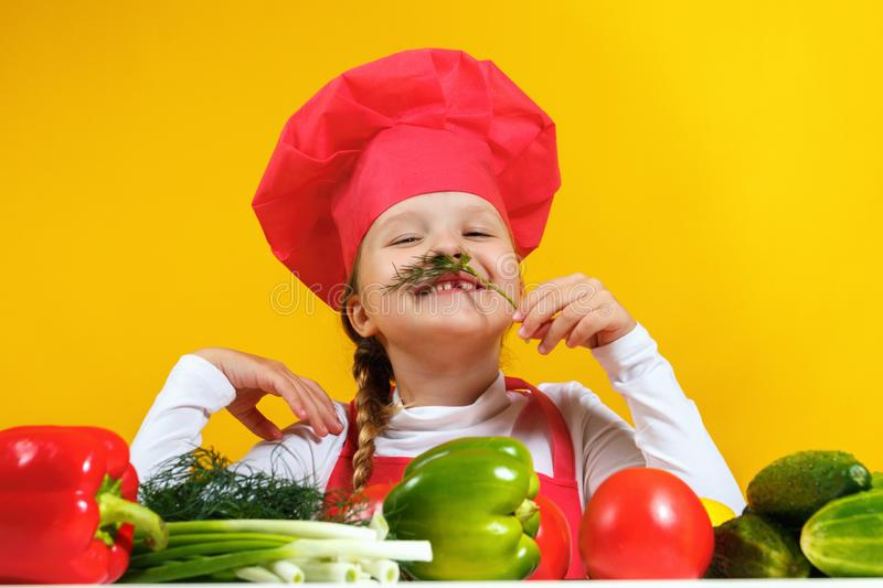 Beautiful little girl chef on a yellow background. A child prepares a vegetable salad, fooling around and making a mustache stock photography