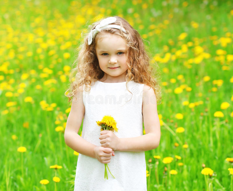 Beautiful little girl child on meadow with yellow dandelion flowers in sunny summer. Day stock image