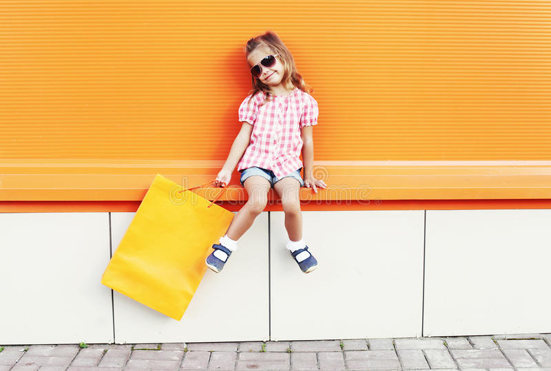 Beautiful little girl child wearing a sunglasses with shopping bags walking in city over colorful orange. Background royalty free stock photos