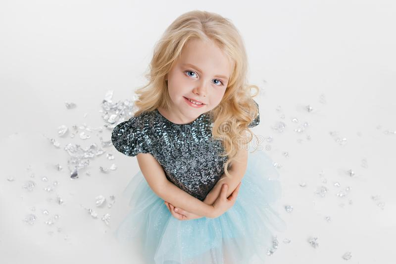 Beautiful little girl with curly blonde hairstyle siting on the holiday party in dress with sequins. Silver foil on the stock photo
