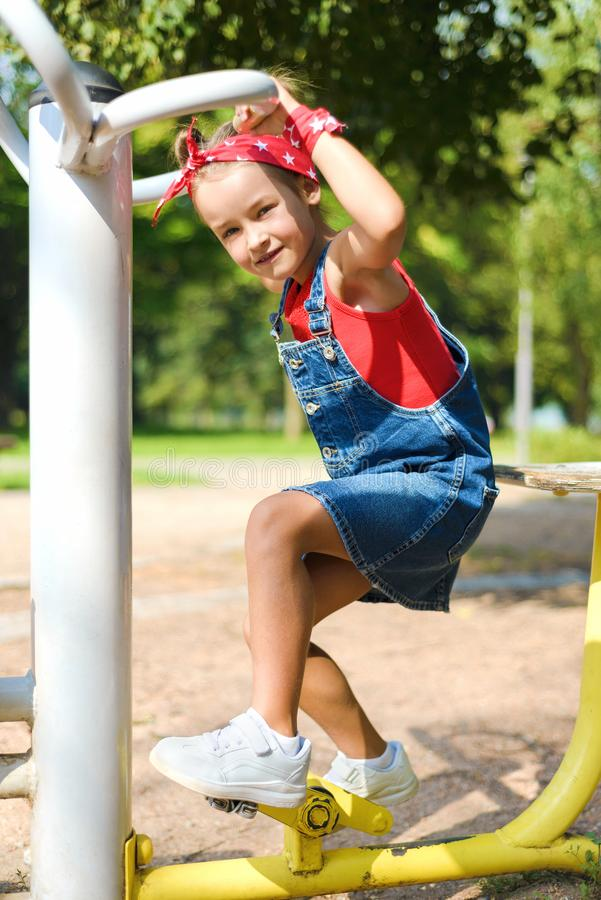 Beautiful little girl in denim overalls and red kerchief is playing at children`s playground stock photography