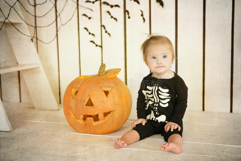 Beautiful little girl with Down syndrome sitting near a pumpkin on Halloween dressed as a skeleton stock photography