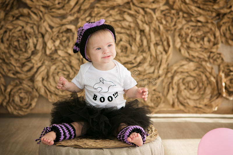 Beautiful little girl with Down syndrome in a suit a little witch stock photo