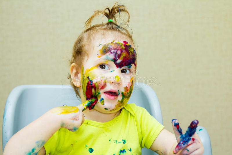 Beautiful little girl drawing in the album, Smeared face and hands paint, eyes. royalty free stock photo