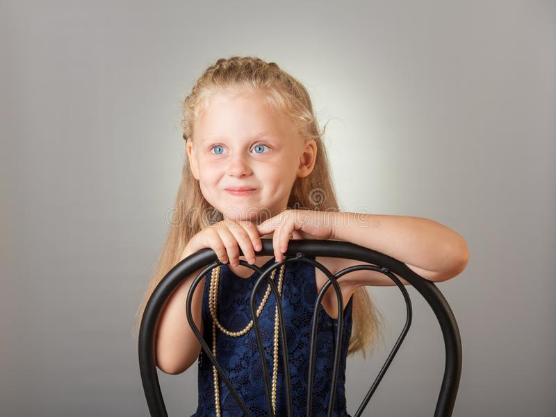Beautiful little girl dressed in a dark dress and jewelry on gray stock photo