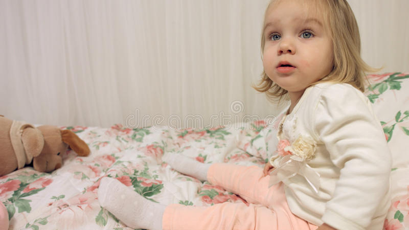 Beautiful little girl dressed in fashionable clothes sitting on couch. Beautiful little girl dressed in fashionable clothes sitting on the couch stock image