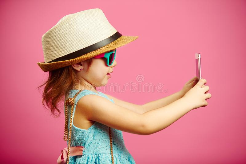 Beautiful little girl dressed in summer dress, wearing a straw hat and sunglasses, makes a selfie portrait on the phone royalty free stock image
