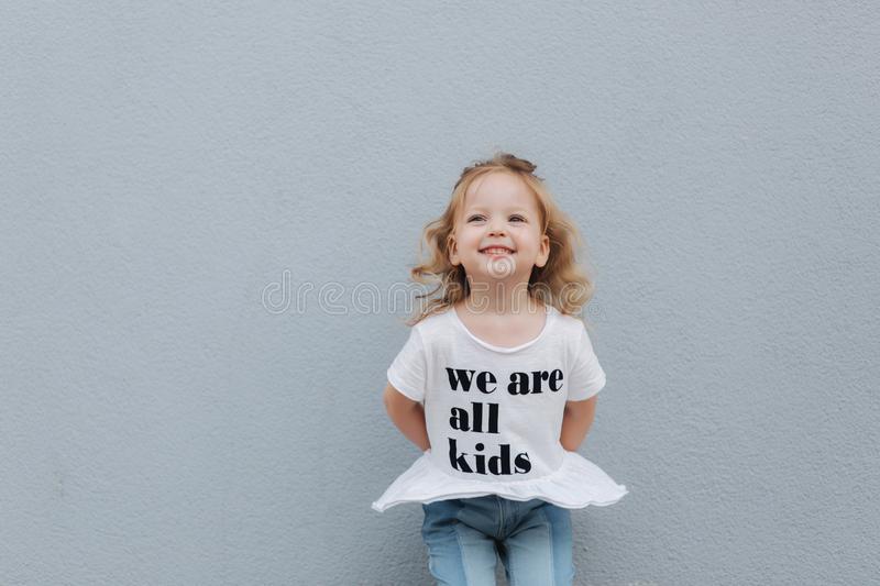 Beautiful little girl dressed in white shirt and jeans stand in front of gray wall. happy children royalty free stock images