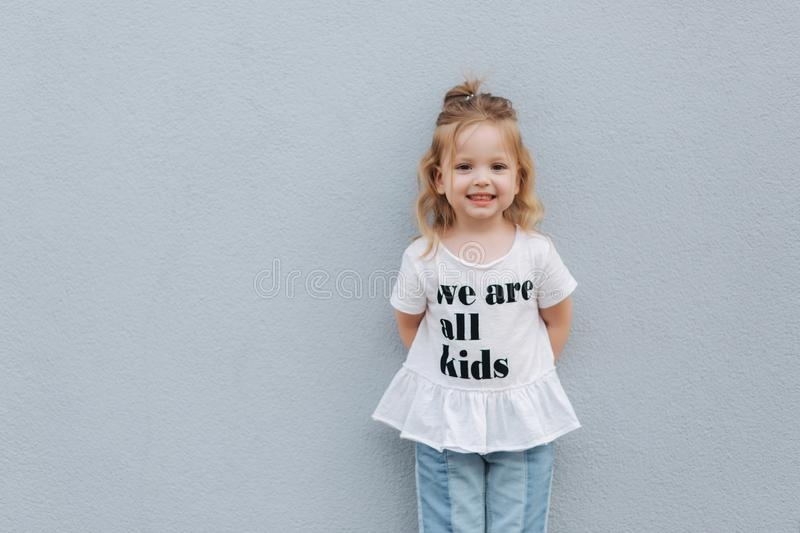 Beautiful little girl dressed in white shirt and jeans stand in front of gray wall. happy children stock photo