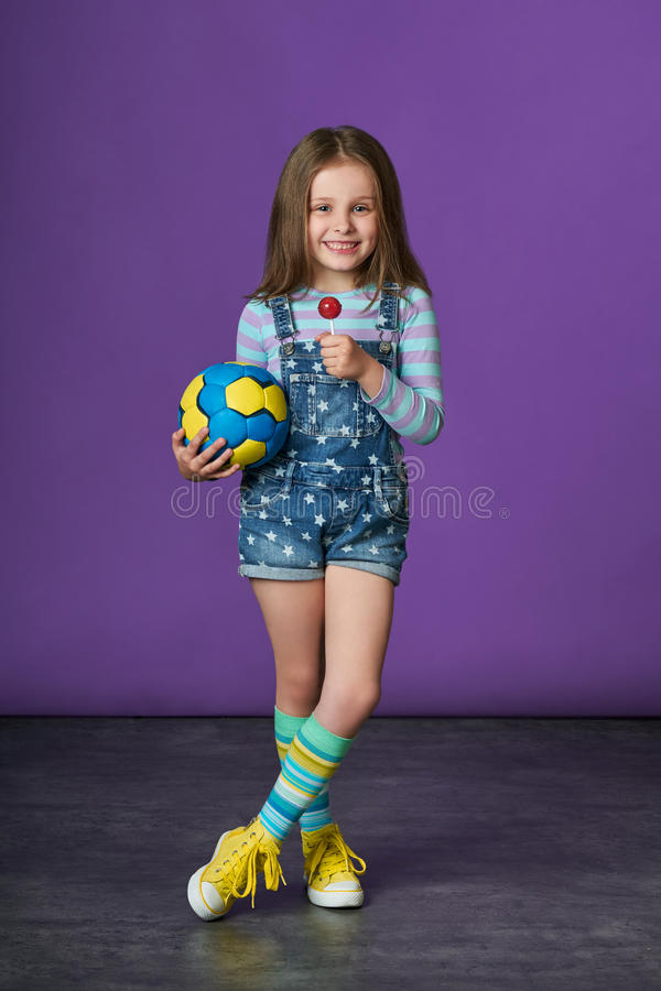 Beautiful little girl eating candy. children`s sports fashion. stock photos