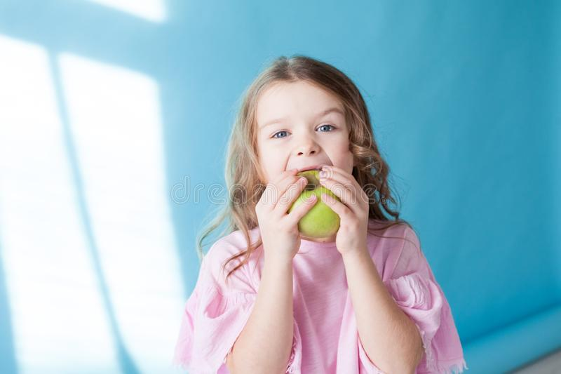 Beautiful little girl eating a Green Apple fruit stock photo