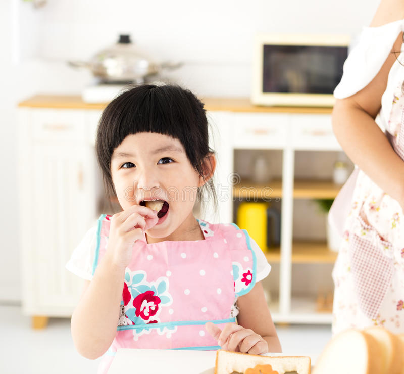 Beautiful little girl eating in the kitchen royalty free stock photos
