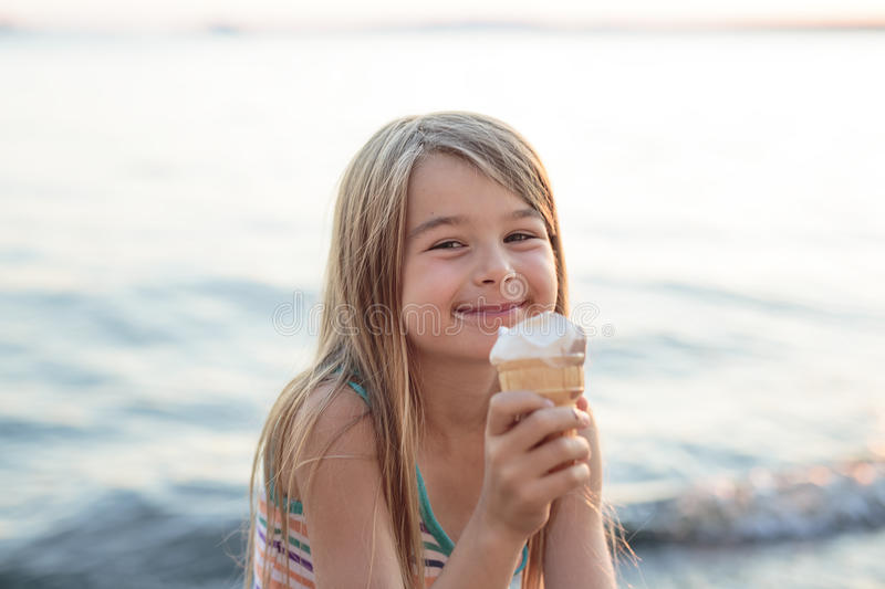 Beautiful little girl eats ice-cream in the summer royalty free stock photos