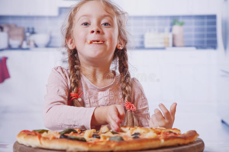 Beautiful little girl enjoying a delicious pizza in nature food stock photo