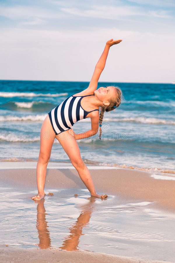 Beautiful little girl excercising on the beach stock photography