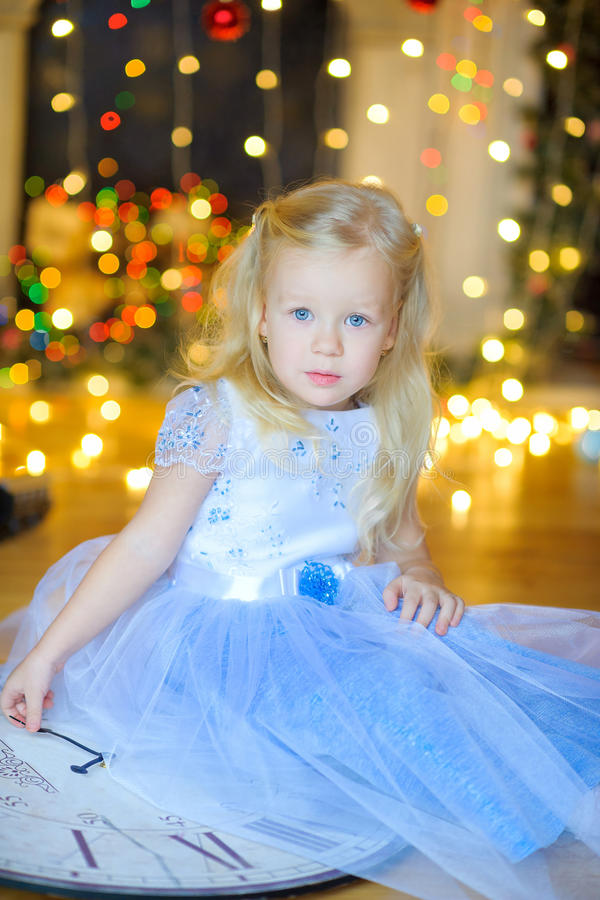 Beautiful little girl in a festive interior. Sits on a floor with gifts in hands. On a background a set of bright sparks. Waiting for a holiday royalty free stock photography