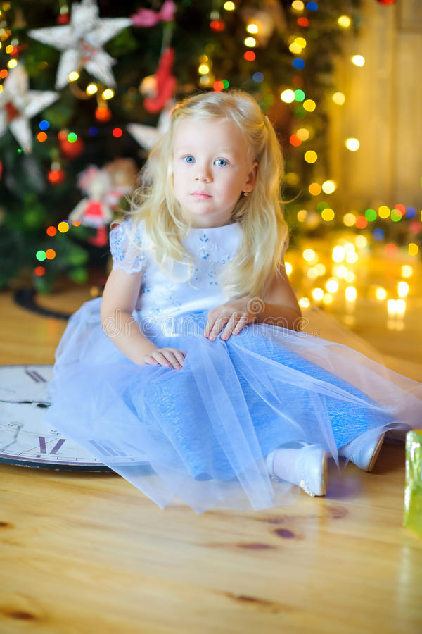 Beautiful little girl in a festive interior. Sits on a floor with gifts in hands. On a background a set of bright sparks. Waiting for a holiday royalty free stock photo