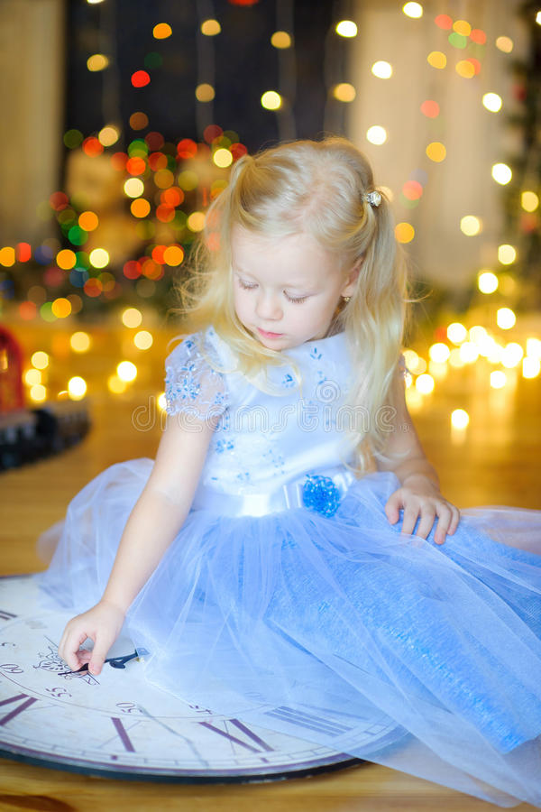 Beautiful little girl in a festive interior. Sits on a floor with gifts in hands. On a background a set of bright sparks. Waiting for a holiday royalty free stock image