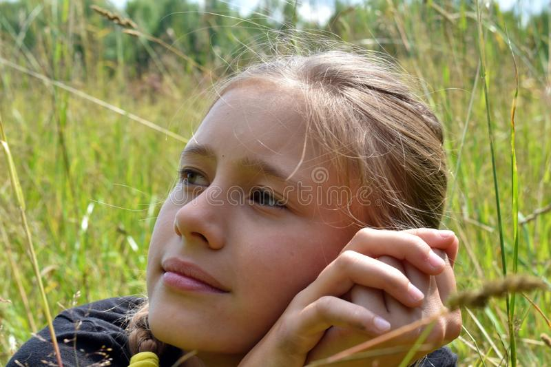 Beautiful little girl with flower in mouth in the forest on summer stock photography