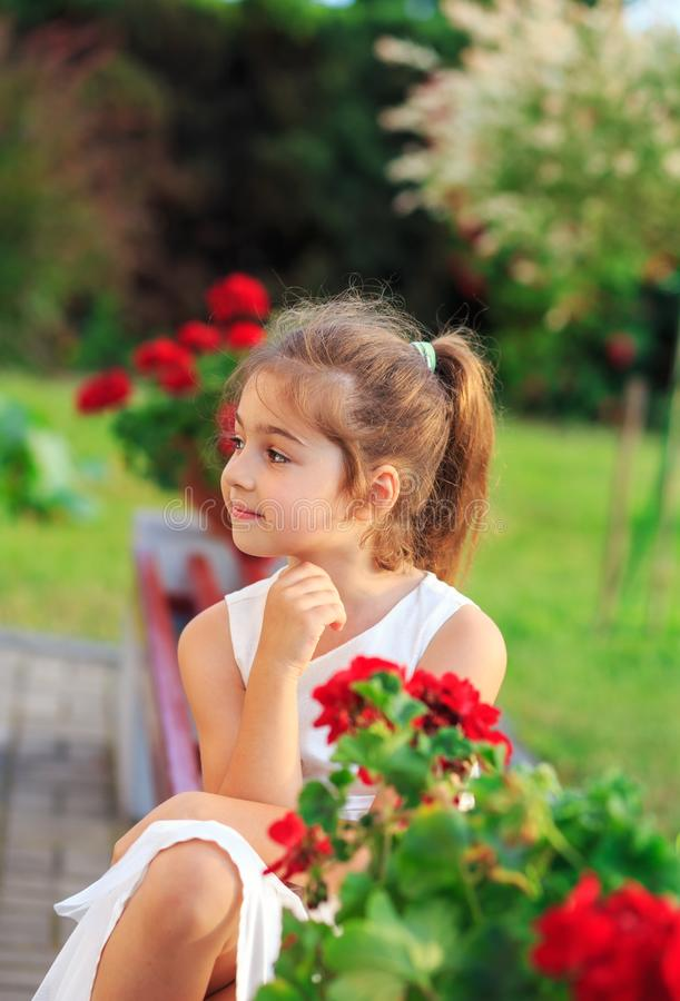 Beautiful little girl with  flowers in sunny summer park. Happy cute kid having fun outdoors at sunset royalty free stock images