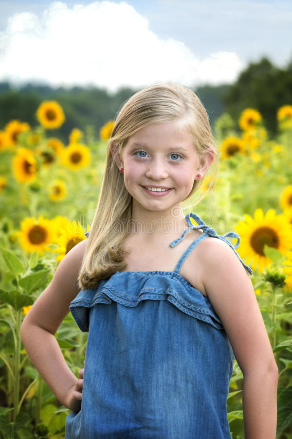Beautiful little girl in front of sunflower field royalty free stock photography