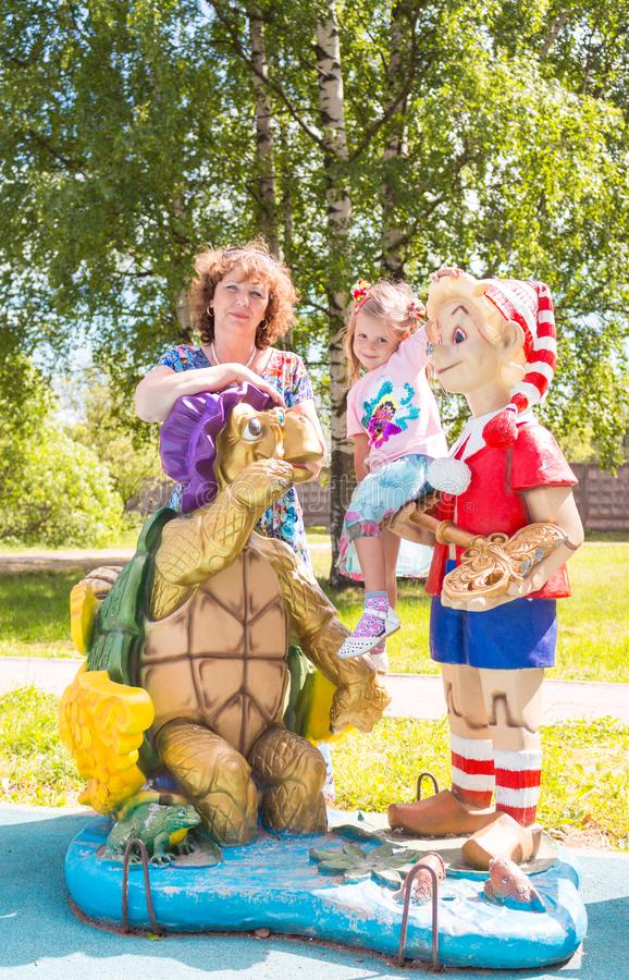 Beautiful little girl with grandmother on the playground with Pinocchio and a turtle royalty free stock photography
