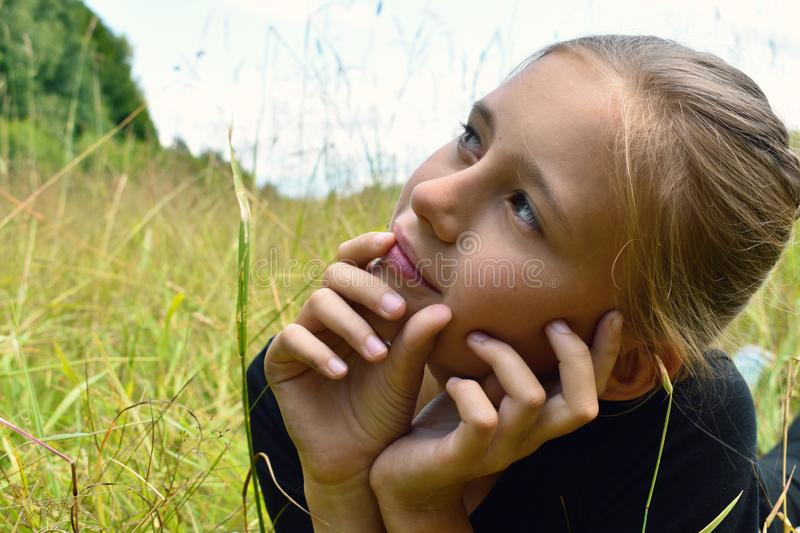 Beautiful little girl in a green grass on summer royalty free stock photo