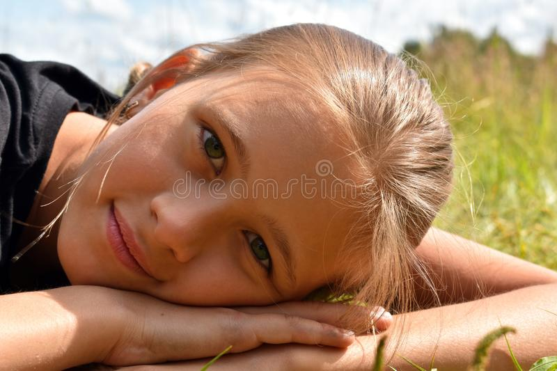 Beautiful little girl in a green grass on summer royalty free stock photography