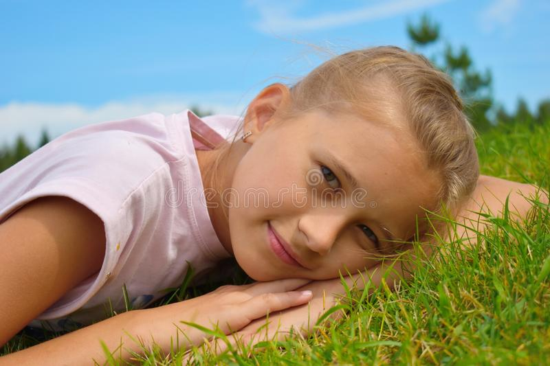 Beautiful little girl in a green grass on summer. Face of the happy child close up royalty free stock photography