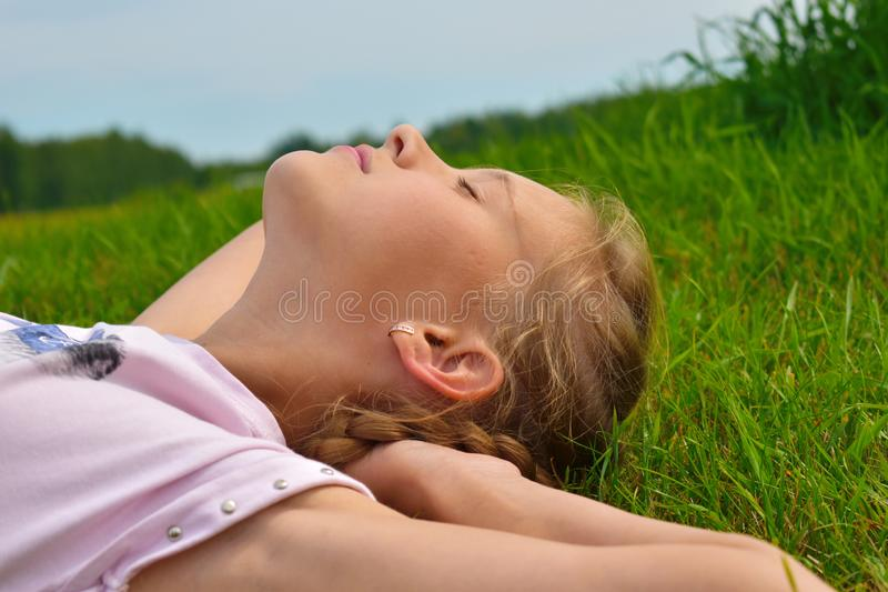 Beautiful little girl in a green grass on summer. Face of the happy child close up royalty free stock image