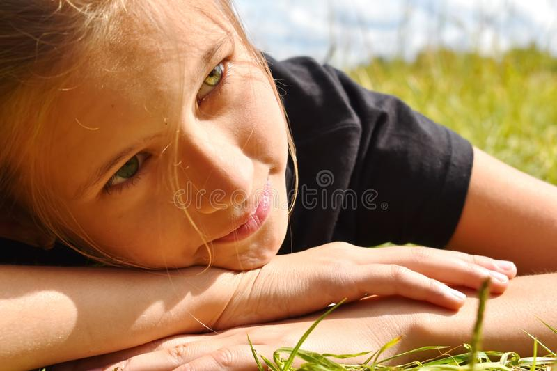 Beautiful little girl in a green grass on summer. royalty free stock photography