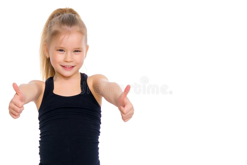 Little gymnast girl shows thumb up. stock photos