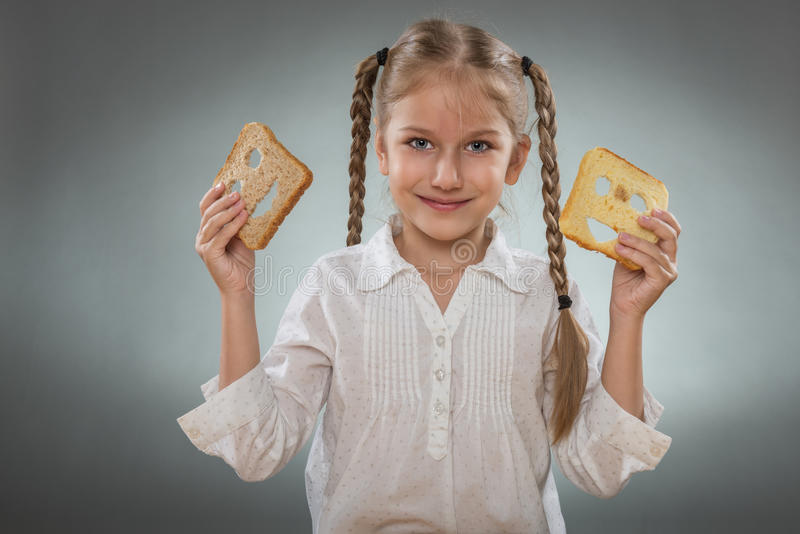 Beautiful little girl with a happy slice of bread royalty free stock image